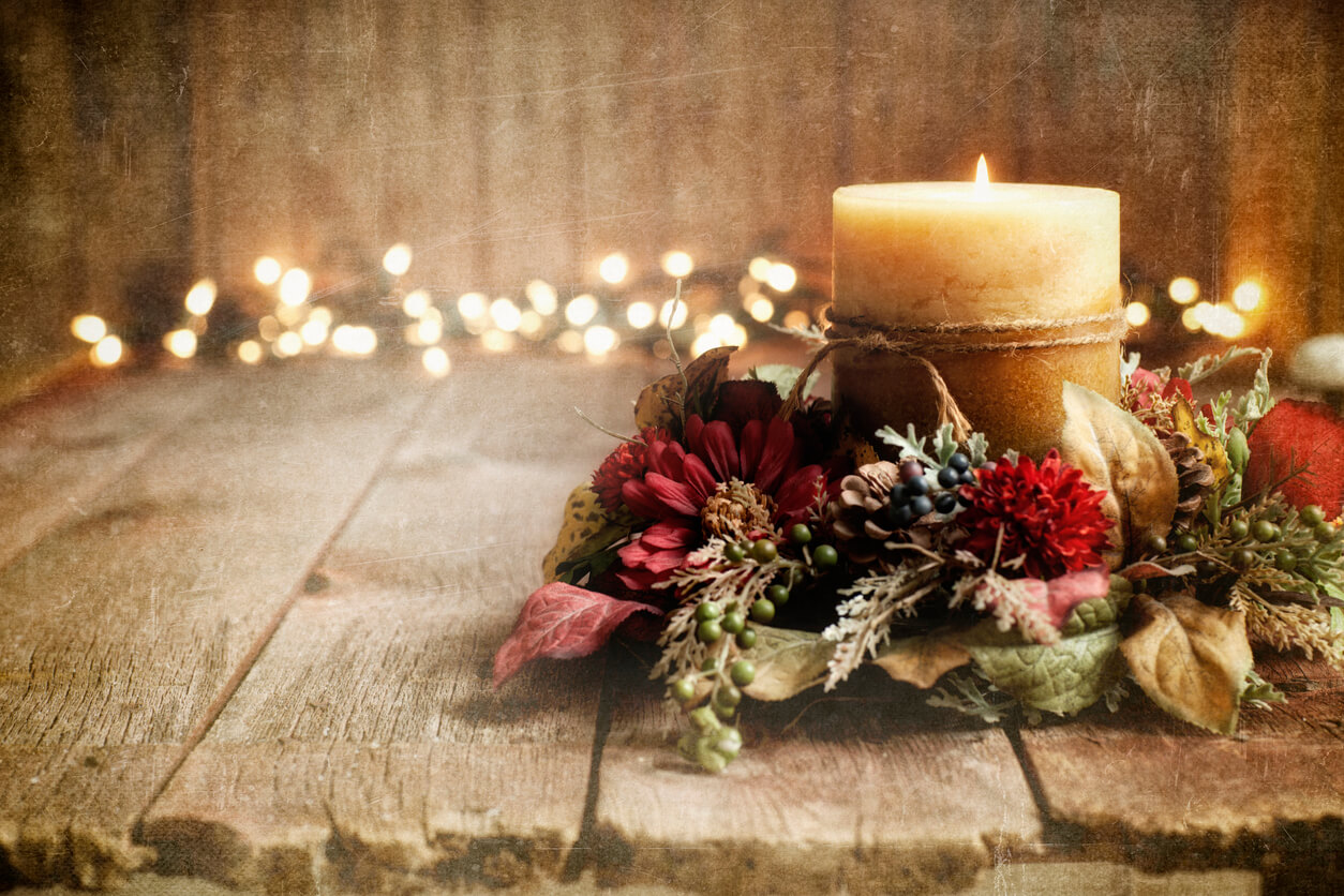 Christmas holiday candle on an old wood textured background