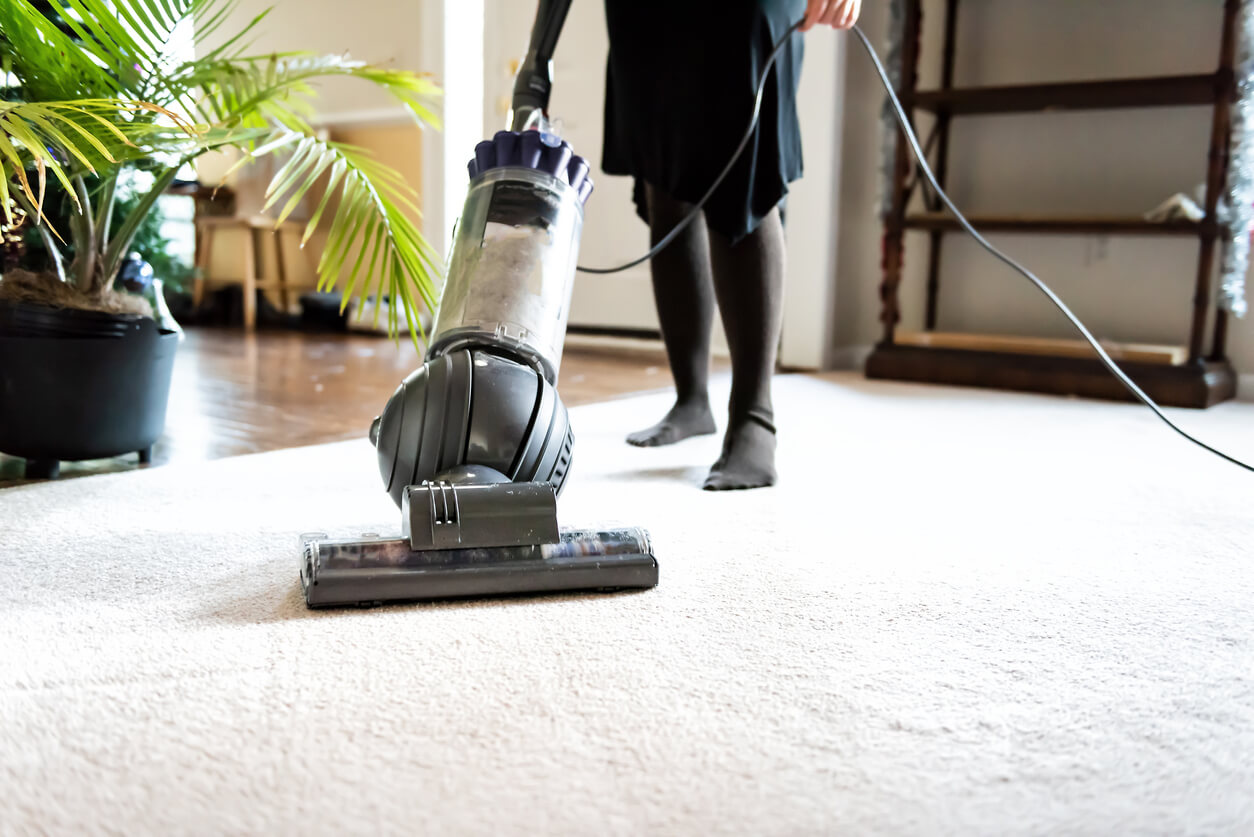 Woman vacuuming to clean her carpet