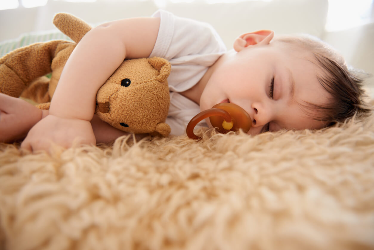 Baby napping on cozy carpet with teddy bear